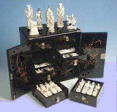 "Japanese or Chinese ivory figural chess set, probably early 20th century, in its original lacquered cabinet. Kings are 5"" high."