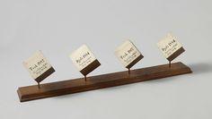 anoniem | Vier houtmonsters van tropisch hout, 1884 | Vier houtmonsters. Vier kubussen van tropisch hout, elk via een stok aan een houten ondergrond verbonden. Op de kubussen staat het soortelijk gewicht en een jaartal. De monsters zijn alle vier gedateerd september 1884.