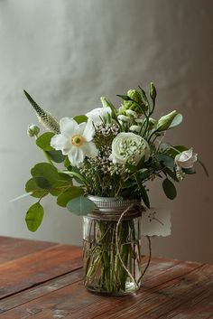green and white floral arrangement in a jar