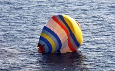 A handout picture taken by the Japan coast guard  shows a hot air balloon which was carrying a Chinese man as it lands on the water, south o...