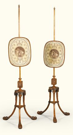 A pair of George III satinwood pole screens, circa 1780, attributed to Thomas Chippendale the younger the oblong screen with print on a turned pole ending on carved block with trophies reliefs, on a circular platform issuing a tripod with carved lion masks monopodiae ending on paw feet and joined by platform stretcher