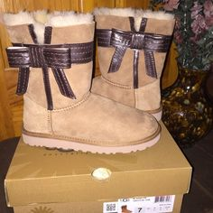 Authentic women's UGG'S size 7 Authentic suede tan UGG with dark Brown leather bow. These Beautiful UGG'S are brand-new. UGG Shoes Winter & Rain Boots