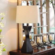 """It's home decor, with a twist! Our """"Espresso Twist Table Lamp"""" combines modern and trendy in one twisting geometrical design that's sure to become your home's next conversation piece. Made out of crafted resin and topped with a cream shade, this lamp is a must-- did we mention it's on sale?"""
