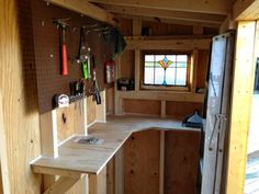Sturdy workbench and peg board to maximize small shed organization space.