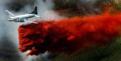 A plane drops its payload of fire retardant on a fire that burns just above homes in the mountains near Alpine, Utah