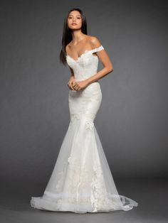 Style 3855 Gisele Lazaro bridal gown - Ivory Chantilly lace mermaid bridal gown layered with Alencon lace applique, strapless sweetheart neckline, off the shoulder cap sleeve, elongated torso, circular tulle overlay with lace applique and bands of horsehair, chapel train.Also available in Ivory Silver/Ivory.Matching Veil L861 -Ivory Alencon lace appliqued cathedral length circular veil with banded horsehair trim.Arriving in stores early Fall 2018