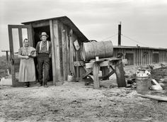 """October 1939. """"Mr. and Mrs. Wardlaw at entrance to their dugout basement home. Dead Ox Flat, Malheur County, Oregon."""" Medium-format nitrate negative by Dorothea Lange for the Resettlement Administration."""