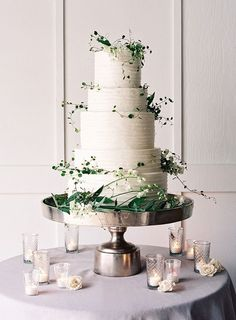Simple and modern white wedding cake with delicate vines and greenery.