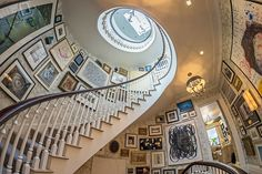Stairwell By: Philip Mitchell Design. Mitchell transformed the showhouse's elliptical stairwell into a glorious gallery of miscellany.  Nearly 300 works of art -- sketches, photographs, watercolors, plaster medallions, and the like -- are clustered on the walls in a heady arrangement that nimbly blends fine paintings with the flea-market finds.  Vases and ojets d'art mounted on brackets fill gaps here and there.
