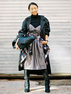 Margaret Zhang wears a turtleneck layered under a printed dress, coat, plaid shirt, quilted leggings, Acne Studios boots, and a black tote