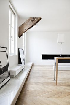 Low marble shelves and herringbone floor. Natural wood beam. Damn.