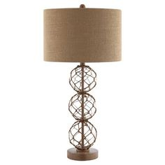 Cast a warm glow in your library or study with this classic table lamp, featuring a glass base accented by knotted rope netting.  Pr...