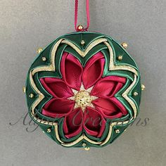 "This unique and elegant ornament was hand-crafted using burgundy and forest green satin ribbon and gold lame fabric. It is embellished with sparkling gold flat back buttons as well as 5mm and 3mm gold balls. The design is the same on both sides of the ornament. The finished product measures approximately 3.5"" (9 cm) in diameter. Each ornament is packaged in its own box for safe shipping and easy gifting. *Due to different setting on various devices, colors may vary slightly from what you…"