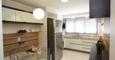 Cozinha com geladeira inox e painel de madeira