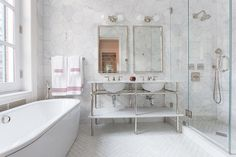 Boasting walls covered in large marble hexagon backsplash tiles, this stunning master bathroom boasts a Waterworks nickel and white marble double washstand sat on white marble herringbone floor tiles under two polished nickel vanity mirrors lit by nickel 2 light sconces.