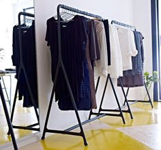 Dresses and blouses displayed on TURBO black clothes racks