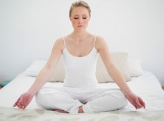woman meditating in her bed