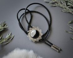 """This celestial Bolo Tie features a round """"half & half"""" stone with jet black at the bottom and clear druzy crystals at the top. This interesting stone is encased in a silver sun burst setting, accented with a black genuine leather cord, silver tie tips and a silver tension clasp."""