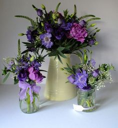 Cream enamel jug and jam jars with purple dahlias and lisianthus, blue scabiosa and white veronica