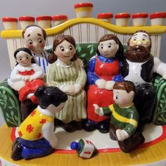 This is a colorful fun menorah ,with a family sitting around watching the kids play with a dreidel.   eBay!