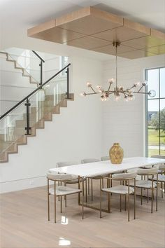 A modern chandelier lights a white and gold dining table surrounded by brass and. - A modern chandelier lights a white and gold dining table surrounded by brass and gray leather dining - Dining Table Lighting, Dining Chandelier, Modern Chandelier, Contemporary Dining Room Sets, Modern Room, Minimalist Dining Room, White Dining Chairs, Dining Room Design, Decoration