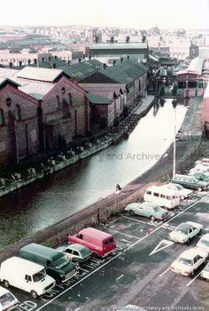 1970s Colour photograph of Pilkington Brothers Limited Watson Street Glass Works, St.Helens. The photograph features St.Helens (Sankey) Canal. STSD/42/54/14 (End of the Canal after that section which was infilled became Canal Street) Sacred Heart Church can be seen in the distance. St Helens Town, Saint Helens, Pilkington Glass, Family Album, The Old Days, Working Class, Sacred Heart, Distance, 1970s