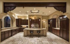 mediterranean-style-kitchen-with-dark-wood-cabinets-and-travertine-flooring This has a weird layout, but I like the custom panel appliances and the beam on the ceiling.