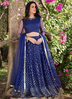Royal Blue and Silver Embellished Lehenga features a dhupioni silk and netblouse, net lehenga with santoon inner and embroidered net dupatta. Sequins and stone embellishments are present all over.