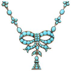 """The Intimate Victorian Turquoise Necklace. Beautiful and symbolic, this turquoise and gold necklace, c. 1860, expresses """"think of me"""" in more ways than one. Small forget-me-not flowers are links on the persian turquoise chain that suspends a bow and a bell...he turquoise stones are matched.The design accentuates the suspended bow by variation in the size of the turquoise. Tiny round stones contrast with the large and bring the bow prominence"""