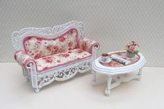 Beautiful Conservatory Sofa consisting of Sofa Upholstered in Pretty Rose Floral Fabric Pink Roses on Ivory Background Oval table with fabric centre covered with perspex Cup of Tea, Newspaper and Vase of Flowers.