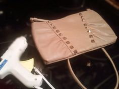 Old nude leather purse from thrift store + studs from cheap costume jewelry + hot glue gun = super cute new purse!