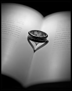 books, rings, shadow heart, and it looks like the profiles of two people in the ring's reflection.