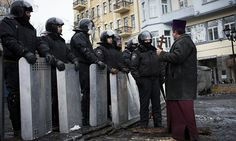 A priest confronts a line of riot police in Kiev. Photograph: Emeric Fohlen/NurPhoto/REX