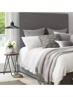 Grey and white bedroom with cute hairpin side table