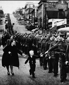 Whitey runs out to grab his fathers hand while the father marches to war. Near Vancouver: 8th Street and Columbia Avenue intersection, New Westminster, Canada October 1, 1940 by Claude P. Dettloff