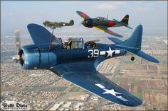 Combat veterans of World War 2: a Douglas SBD-5 Dauntless, Mitsubishi A6M5 Zero, and Curtis P-40N Warhawk fly in friendlier times over Chino, California.