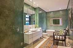 This cozy bathroom in jungle green tones features striking white floating vanity with wide vessel sink, an all-glass shower enclosure, and deep soaking tub at far end. Bamboo chair and patterned rug add texture.