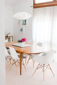 Mid-century dining space with a pendant and white Eames inspired chairs.