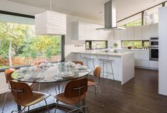 Without increasing the size of the kitchen, we reworked the space to create a family friendly design. This was accomplished by moving the range to the island, adding counter seating and increasing storage with full height cabinetry. New larger windows were added in the dining room to replace small punch openings and natural lighting in the kitchen was improved by adding low counter height windows.