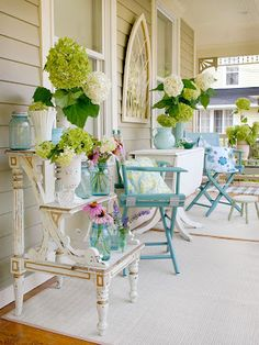 Beautiful porch: blue mason jars filled with wild flowers atop a vintage step-ladder side table (WANT!). Also, gotta love the turquoise director's chairs, cathedral-style mirror and giant hydrangea blooms.
