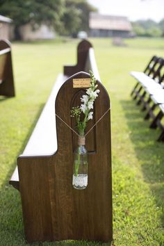 Wedding decor idea: bottles of garden flowers tied with twine and wrapped with crocheted lace hang from vintage wooden church pews.    Glamorous, Vintage, Rustic Texas Barn Wedding | Venue: Cherokee Rose