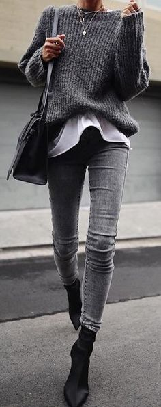 #spring #outfits woman in black sweater, black leather crossbody bag, and grey denim jeans walking on concrete pathway during daytime. Pic by @speak__style