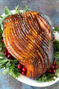 A glazed ham on a serving platter garnished with cranberries and fresh herbs.