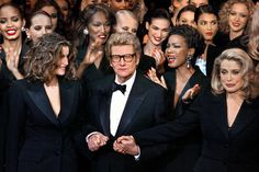 Yves Saint Laurent: Yves Saint Laurent with models Laetitia Casta, Mounia, and Katoucha during his last Haute Couture show in January 2002.