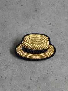 By Macon & Lesquoy.Inspired by the precision and quality of military embroidery.This golden boater hat is hand embroidered in bullion stitch to achieve a 3D effect along with amazing detail.