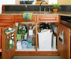Commandeer the Sink Cabinet Intrusive plumbing pipes, the sink bottom, and pullout hoses can make bringing order beneath the kitchen sink a particular challenge. Choose stackable acrylic or wire shelving that fits beside and below the sink U pipe to make the most of available space. Some wire bin units slide out to make it easy to retrieve items at the back. Add storage bins, shelves, and hooks inside doors for more storage, and consider including some specialty storage such as a holder for…