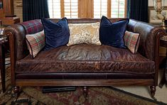 Classic brown leather sofa/settee with single seat cushion and tartan throw pillows - Nell Hill