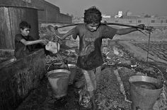 Nawab Ali (12 years old) carries buckets full of glue manufactured from waste leather and hides, while Jabar (14 years old) fills other buckets standing inside a glue tank in the background. Photography by Shehzad Noorni