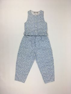 Blue Floral Sun Set   Your little girl will breeze through those steamy hot summer days in comfort and looking adorable. The same 100% cotton print as our Blue Floral Pinafore Dress. Very full pull-on pants with elasticized waist, roll up cuffs. waist length top with ruffle, button front, sleeveless, rounded neckline. Machine washable.