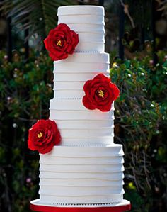 Red flowers on banded white wedding cake